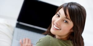 Portrait of a happy young female using a laptop